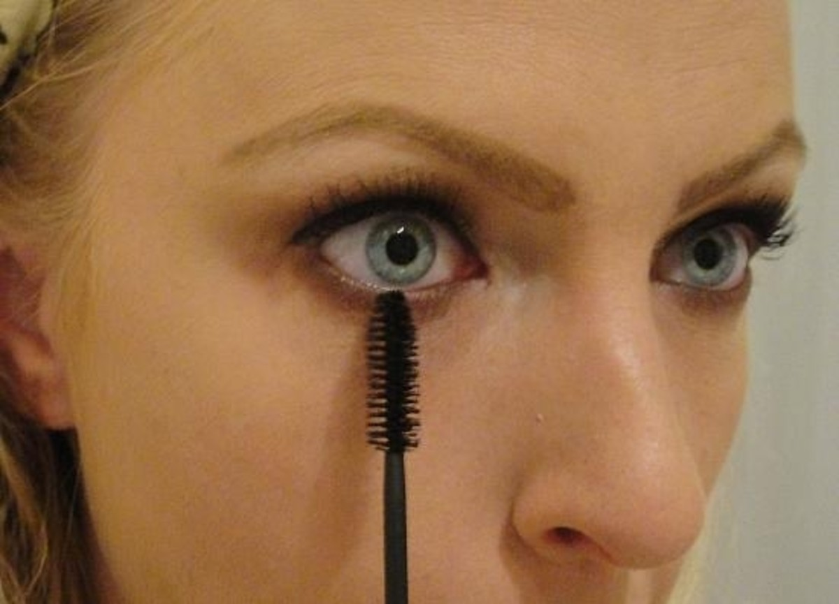 Woman Applying Mascara To Lower Lashes