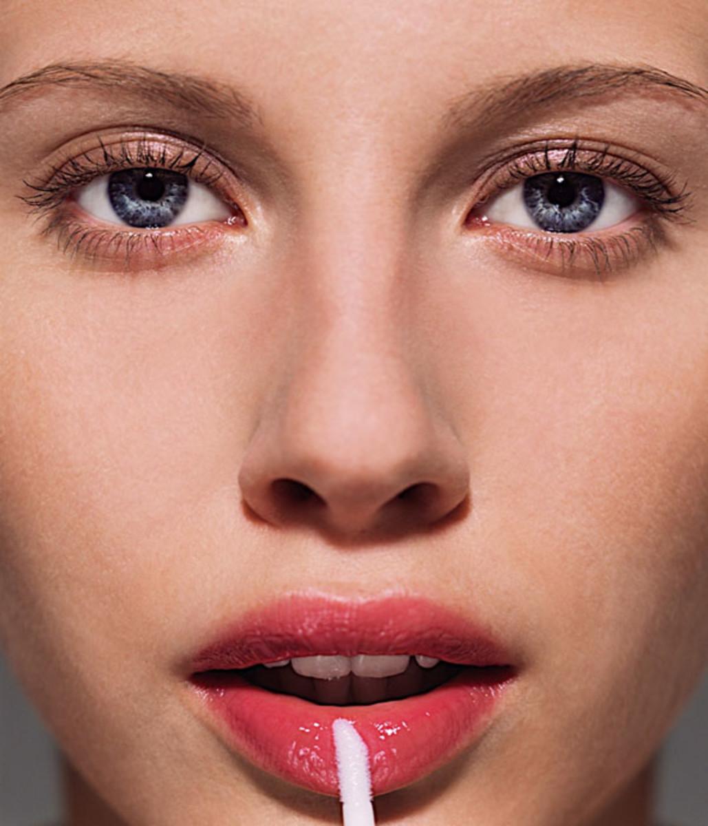 woman-applying-lip-gloss